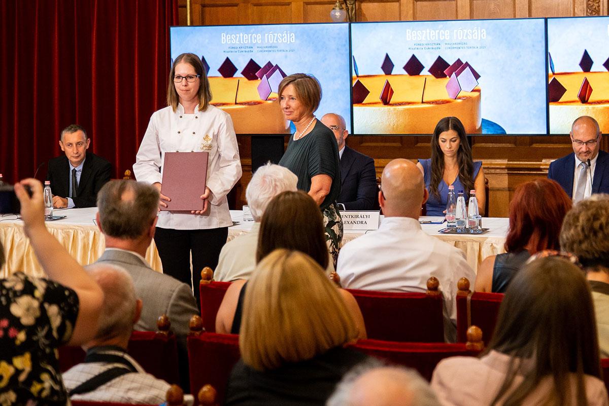 Lopes-Szabó Zsuzsa átadja a különdíjat a torta készítőjének
